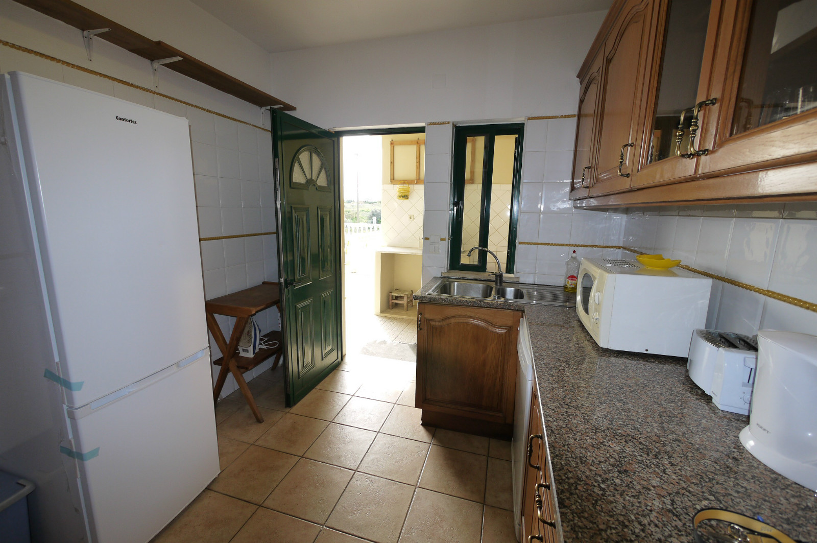 The compact, and complete kitchen, has good views and door to terrace & BBQ.