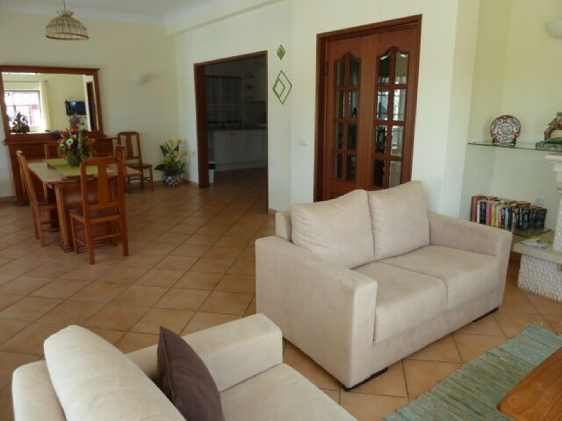 Cosy lounge with a satellite TV, overlooking dining room, kitchen & pool