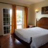 1st floor a/c bedroom with double doors to private balcony overlooking pool.