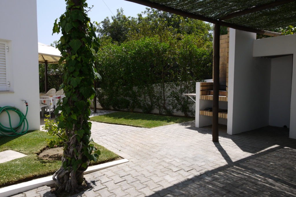 Large outdoor BBQ, with private parking for several cars including covered area.