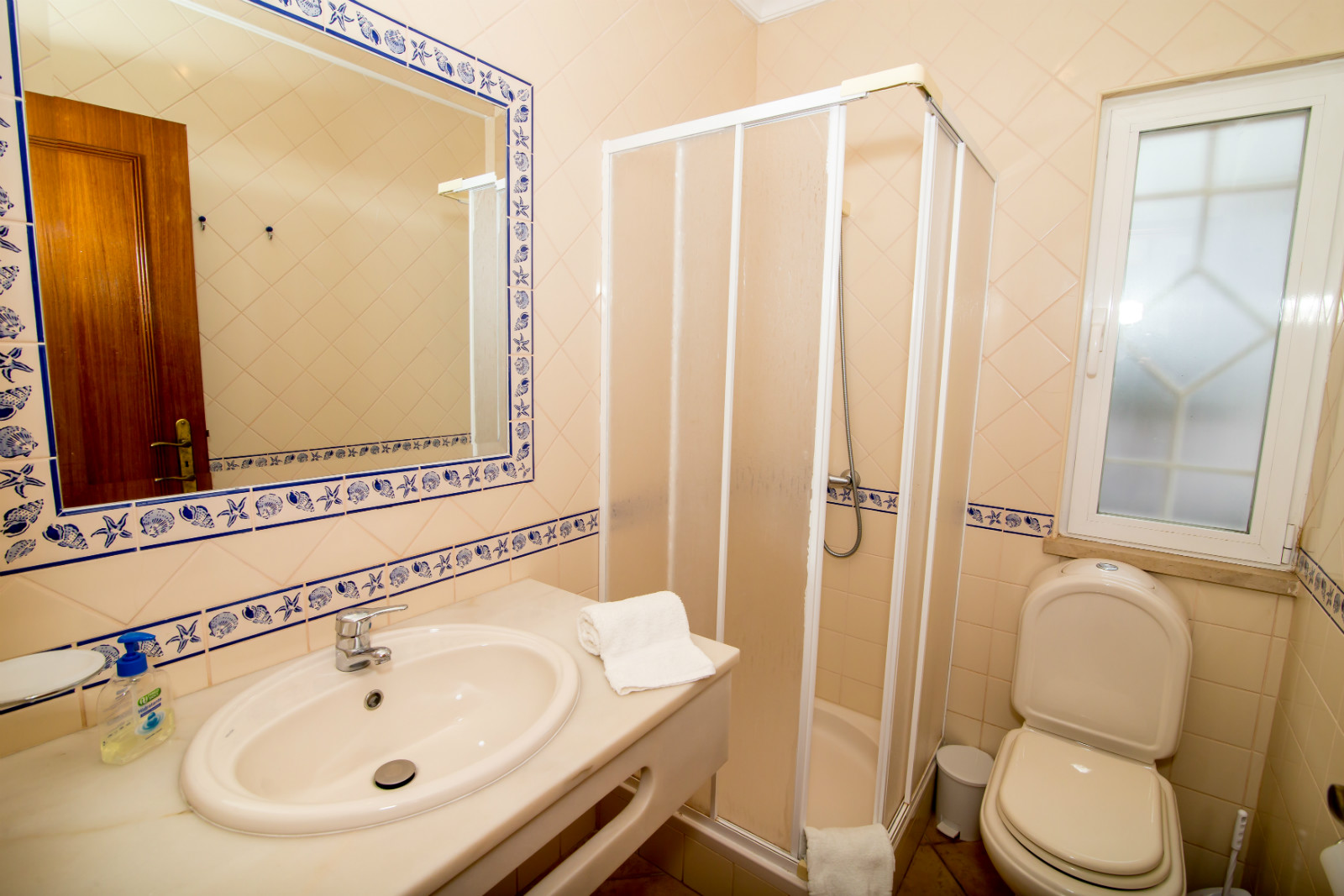Ground floor private, light & bright bathroom with shower, w.c. & marble basin.