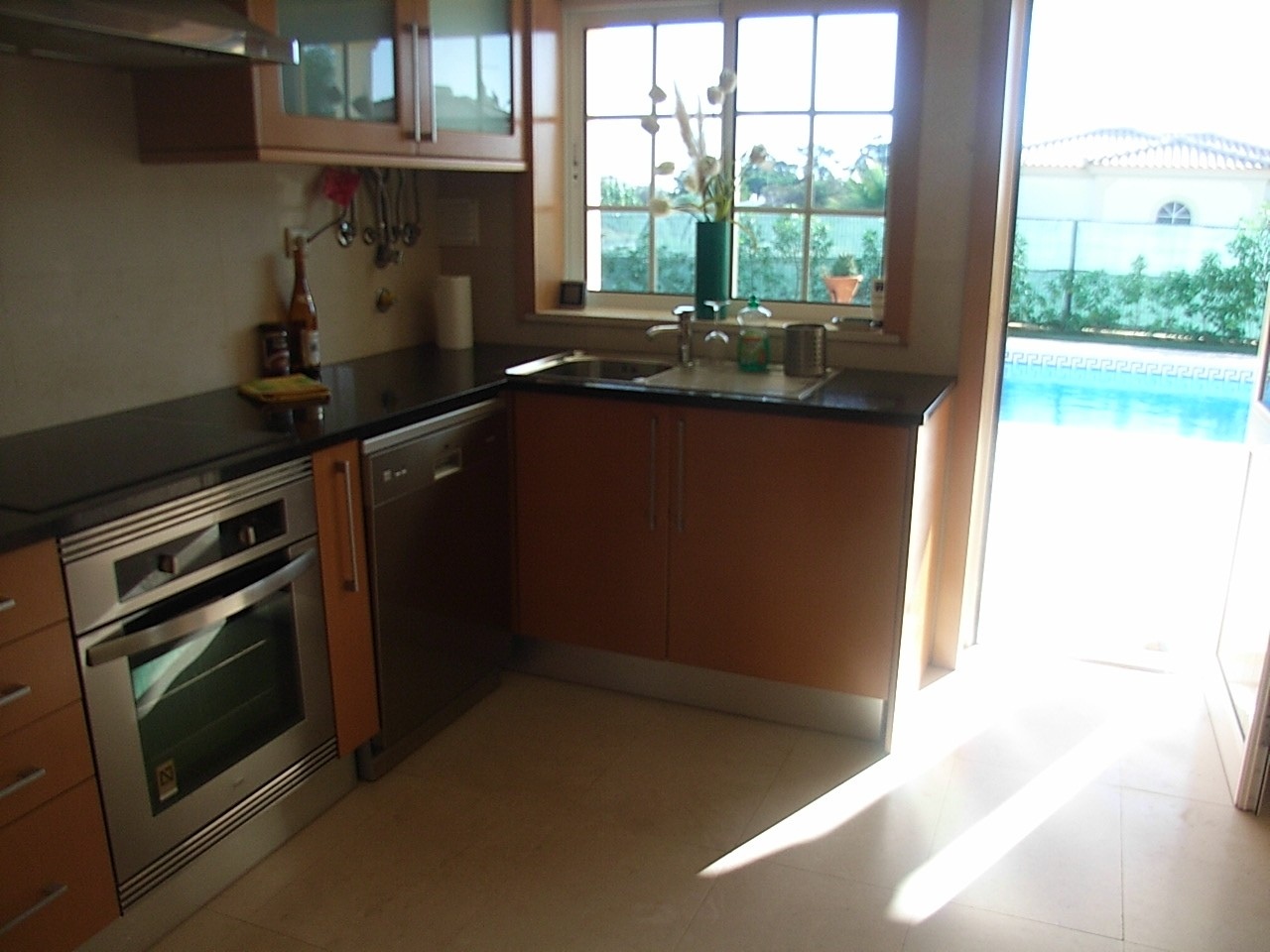 Fully equipped kitchen with sea views, overlooking pool & established garden.