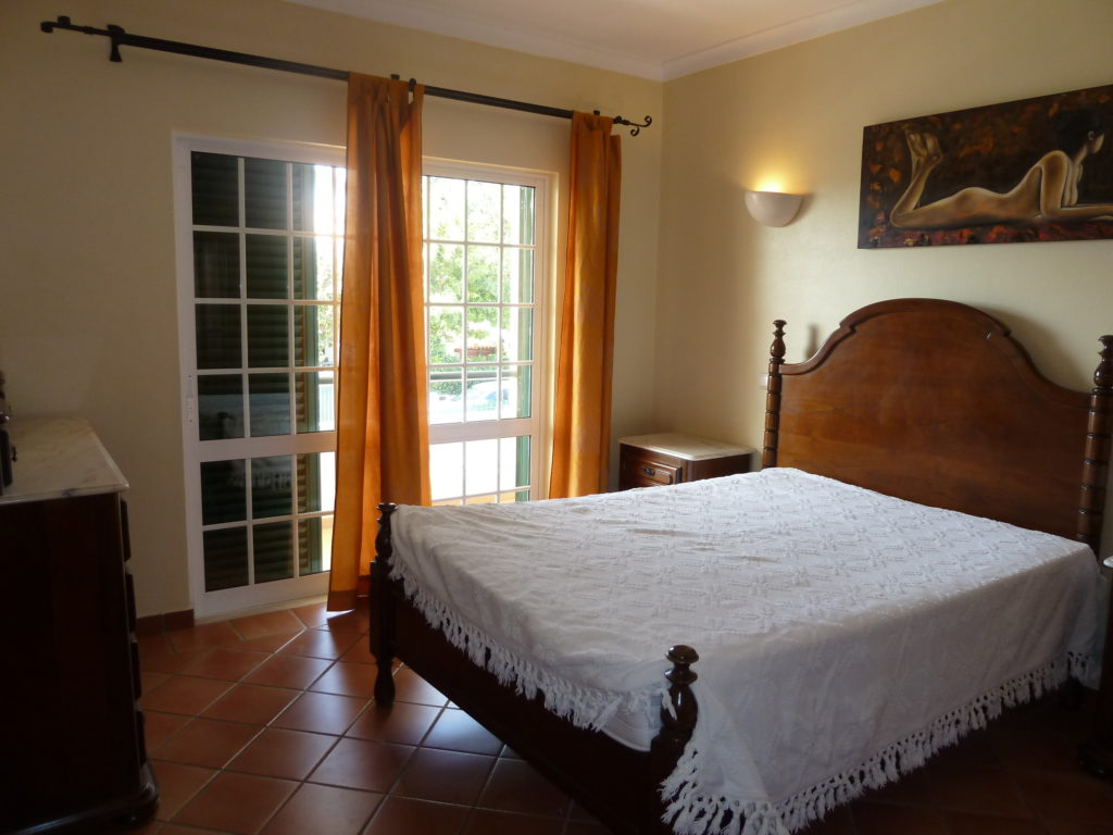 1st floor a/c bedroom with double doors to private balcony overlooking pool.